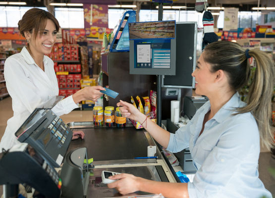 Clerk taking card from customer to complete purchase